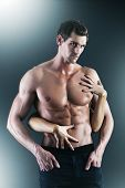 Sexy muscular naked man and female hands holding his chest