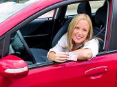 a young woman proudly displays her license. license and new car.