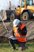 Site surveyor taking readings