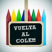 sentencia de regreso a la escuela, escrita en español, vuelta al cole, en una etiqueta de pizarra y algunos lápices de colores o