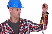 Wide-eyed tradesman staring at a multimeter