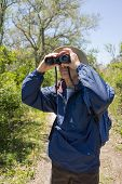 Man Hiking, Birdwatching And Looking Through Binoculars