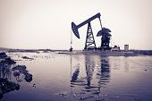 image of oilfield  - Oil pump jack and reflection - JPG