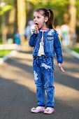 foto of finger-licking  - Pretty little girl licking her own fingers after eating cotton candy  - JPG