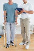 Low section of a male therapist and disabled patient with reports in the gym at hospital