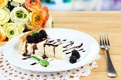 Slice of cheesecake with chocolate sauce and blackberry on plate, on wooden  table, on bright backgr
