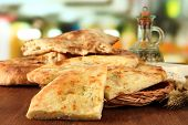 stock photo of flat-bread  - Pita breads on wooden stand with oil on table on bright background - JPG