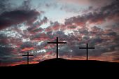 Resurrection - Hillside with three empty crosses and dramatically colorful clouds.