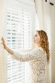 pic of lace-curtain  - Happy woman looking out big bright window with curtains and blinds - JPG