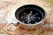 foto of cardinals  - Handheld compass lying on a map showing the needle and cardinal points of north south east and west to aid in magnetic navigation to plot a route or direction to a specific destination - JPG