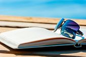 stock photo of protective eyewear  - open book and sunglasses on the background of the sea