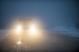 foto of slippery-roads  - Bright headlights of a car driving on foggy winter road - JPG