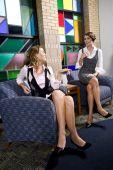 stock photo of legs crossed  - Attractive happy young women wearing skirts sitting in armchairs in reception area - JPG