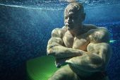 Bodybuilder with closed eyes in pool underwater among many small bubbles
