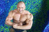 Top view of happy middle-aged bodybuilder standing in swimming pool