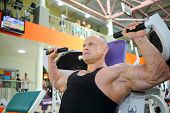 Bodybuilder in black jersey trains on exercise machine in gym hall and looks away
