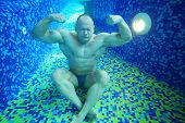 Bodybuilder in swimming trunks sits on bottom of pool underwater