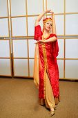 Pretty woman in red Andalusian costume dances with shawls in hands