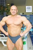 Happy sunburnt bodybuilder stands near indoor pool in big modern gym hall