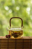Transparent teapot with blooming tea flower on green natural background