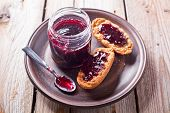 black currant jam in glass jar and crackers on rustic wooden board