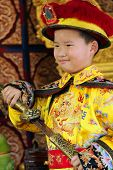 Beijing, China - Jul 4, 2011: Chinese Boy Dressed As Emperor With A Sword. To Take Photos Of Childre