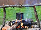 stock photo of kettles  - smoked tourist kettle over campfire - JPG