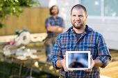 Portrait of mid adult carpenter displaying digital tablet with coworker in background at constructio