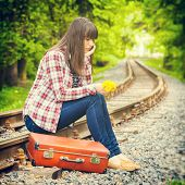 Sad Girl With Suitcase And Bouquet Of Dandelions Sitting On The Rails