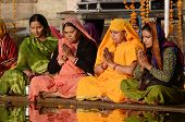 senior women perform puja - ritual ceremony at holy Pushkar town,India