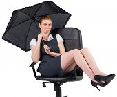 Businesswoman holding umbrella sitting on swivel chair on white background