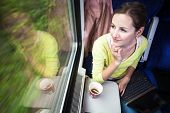 Young woman traveling by train (landscape moving fast behind the window (<--- motin blurred image)