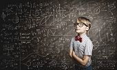 Genius boy in red glasses near blackboard with formulas