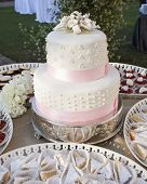 two tiered wedding cake with pink ribbon