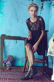 Beautiful blond woman with braid hairstyle and natural makeup. Wearing lace black dress and boots. A