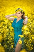 Fashion beautiful young woman in blue dress and yellow flowers wreath posing outdoor in canola field