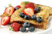French toast with cinnamon, strawberries and blueberries.