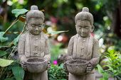 picture of garden sculpture  - Stone sculpture of kids holding bowl in the garden - JPG