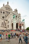 Tourists Walking Near Sacre Coeur Basilica In Paris
