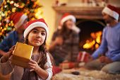 Little girl in Santa cap with giftbox on background of her parents and brother