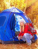 Happy young traveler relaxing in the camp in bright sunny autumn day, discovering nature, expedition in the forest, active lifestyle concept