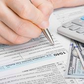 stock photo of cpa  - Male filling out 1040 Tax Form - studio shot