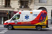 MADRID, SPAIN - OCTOBER 9, 2014: An ambulance speeding through the streets of Madrid. Due to Spanish law, only police use blue lights and ambulances and fire engines have to use amber lights.