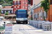 PAXOS, GREECE - JUNE 14, 2014: The local island bus negotiates the narrow seafront road at Loggos on the Greek island of Paxos. Taverna diners have to vacate their chairs to let the bus pass.