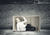 Young businesswoman trapped in carton box