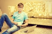 Casual young man sitting on the floor with a laptop in the comfort of his home.