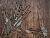 faded colors of a set of vintage chisels and sharpening stones, strop over wooden bench, space for your text