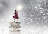 Young woman in blindfold standing on pile of books