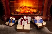 Christmas gift boxes and warm fireplace at evening