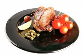 grilled beef meat medallion with  tomatoes on black plate